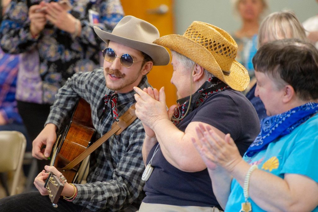 Man plays guitar for people at Friendship Towers