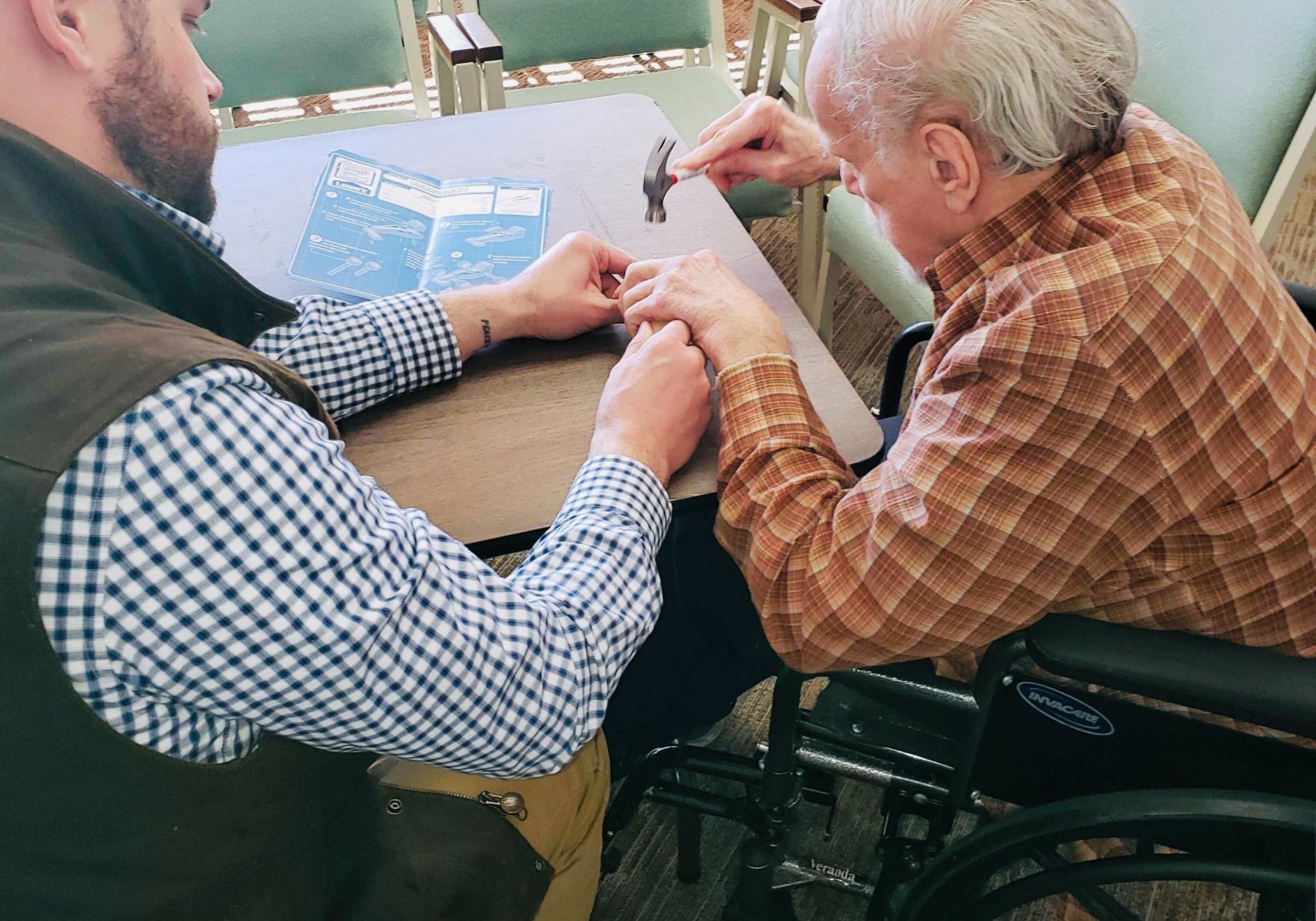 Man helping elderly man